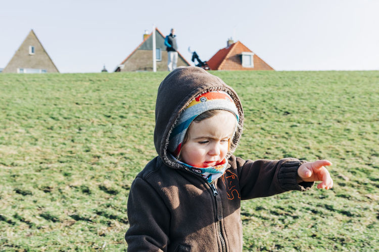 Close-Up Of Girl Pointing While Standing In Warm Clothing On Grassy Field