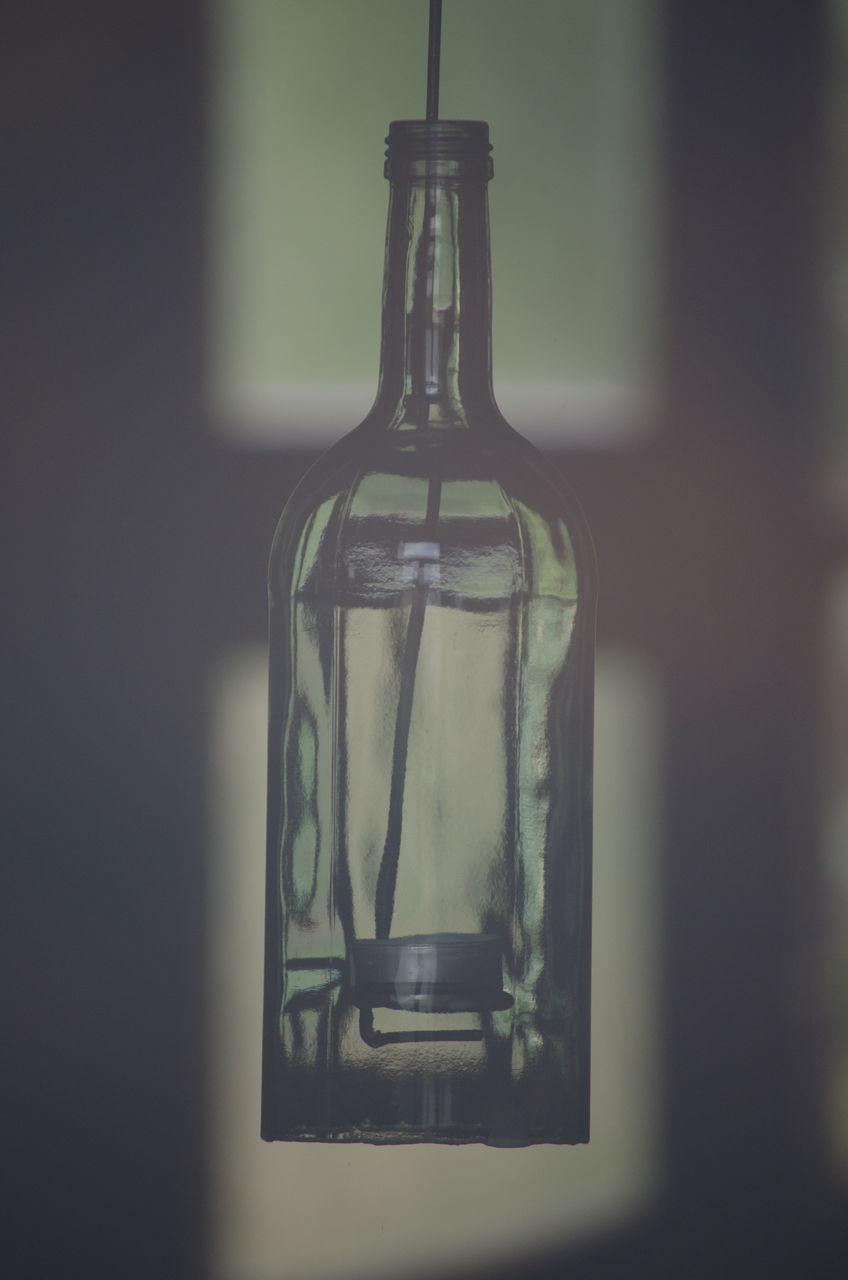CLOSE-UP OF GLASS BOTTLE ON TABLE AGAINST WINDOW