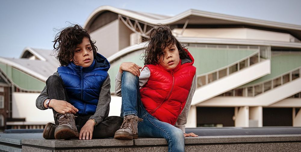 Full length of boys sitting on built structure