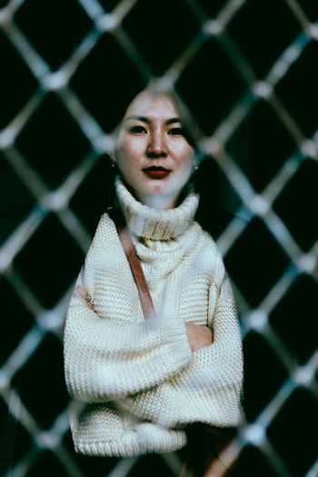 Portrait of woman seen through fence
