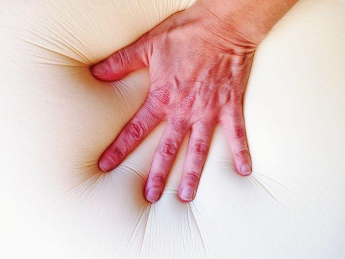 Close-up of hand touching mattress
