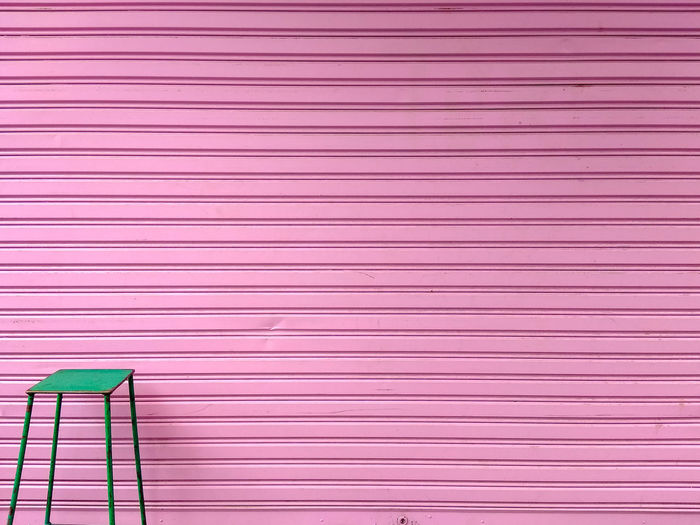 The green chair is in front of the pink wall. Minimal style. Pink Color Pattern No People Full Frame Backgrounds Shutter Wall - Building Feature Copy Space Metal Multi Colored Textured  Built Structure Close-up Architecture Day Red Closed Wood - Material Striped Outdoors Iron Minimalism