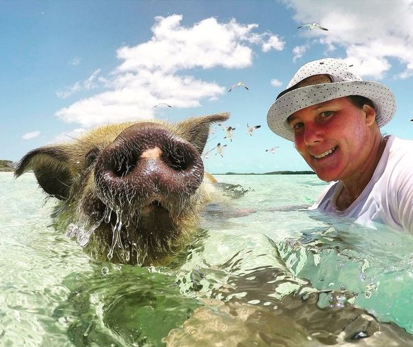 Portrait of smiling young woman swimming in sea with pig