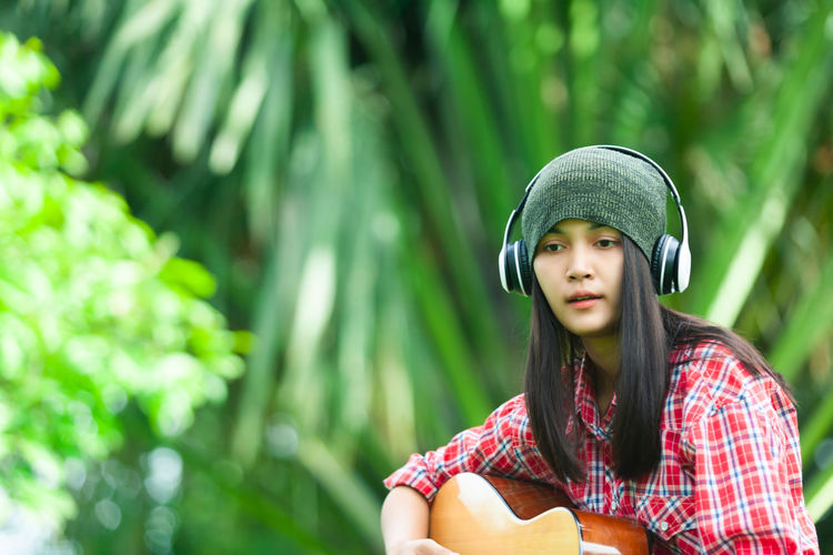 Young Woman Playing Acoustic Guitar While Sitting At Park