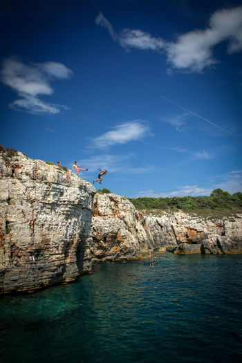 Three men jumping from cliff