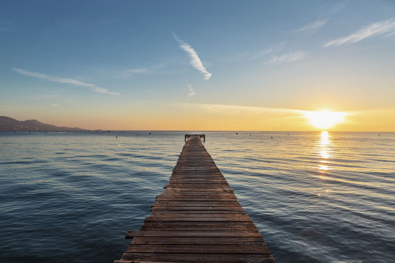 Wooden Pier On Sea Against Sky During Sunset