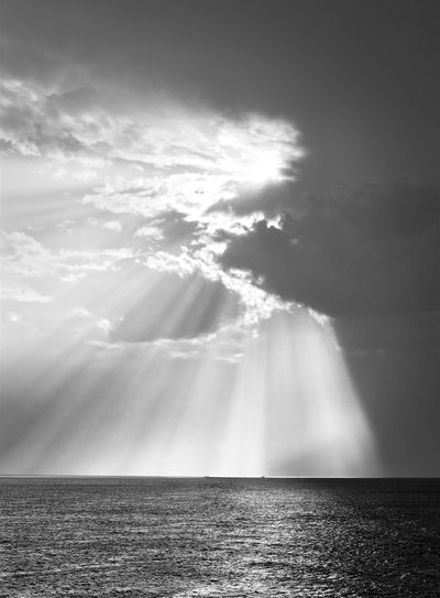 Sunlight streaming through clouds over sea
