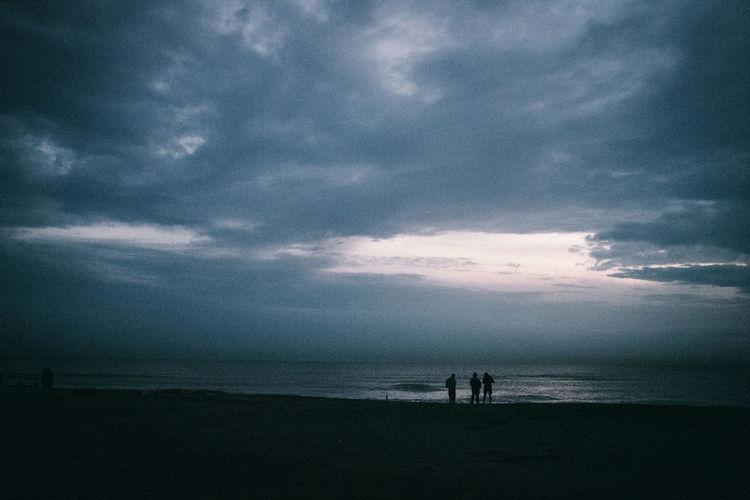 Silhouette people on beach against sky at dusk