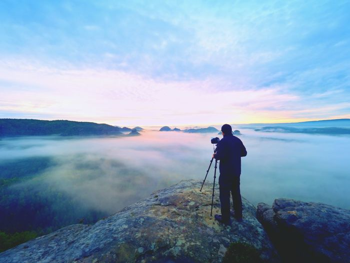 Man photographing on rock against sky