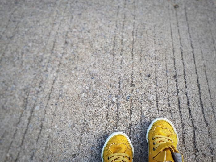 Yellow shoes on footpath