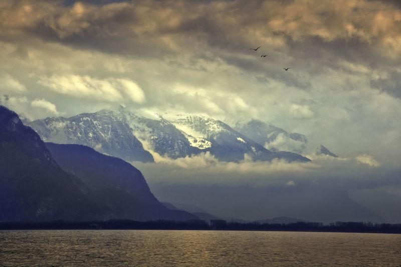 Idyllic shot of lake geneva and mountains against cloudy sky