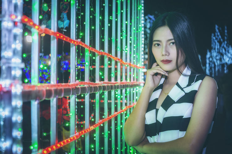 Portrait of beautiful young woman standing against illuminated bridge