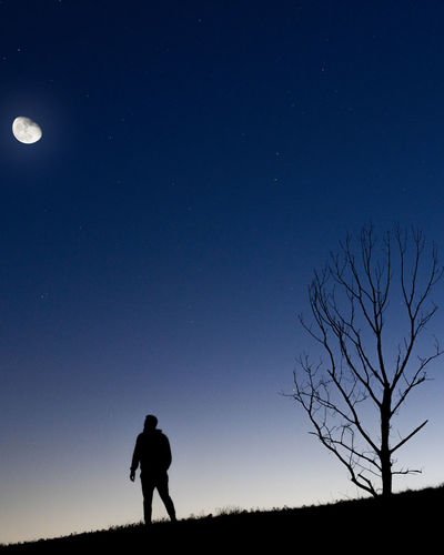 Silhouette men on field against sky at night