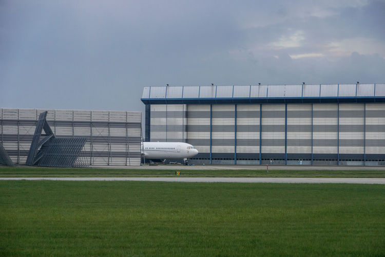 Airplane on runway in front of warehouse against sky
