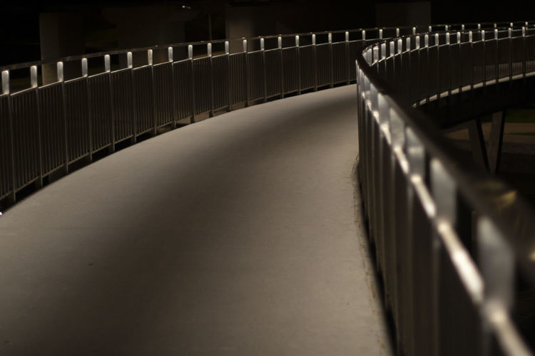 Park path at night. the light of the fanars on the embankment bridge. path in the dark.