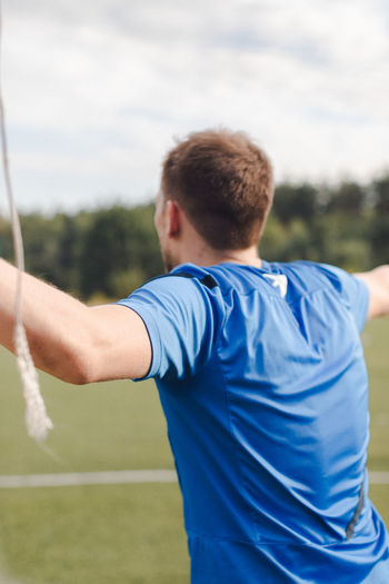 Rear view of man playing on field