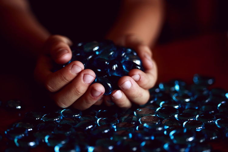 Abundance Azul Beads Black Color Blue Child Close-up Darkness And Light Fingers Glass Hand Holding Large Group Of Objects Part Of Person Selective Focus Shiny Treasure Unrecognizable Person Colour Of Life