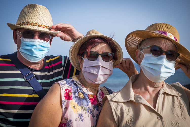Portrait of senior people wearing sunglasses and mask standing outdoors