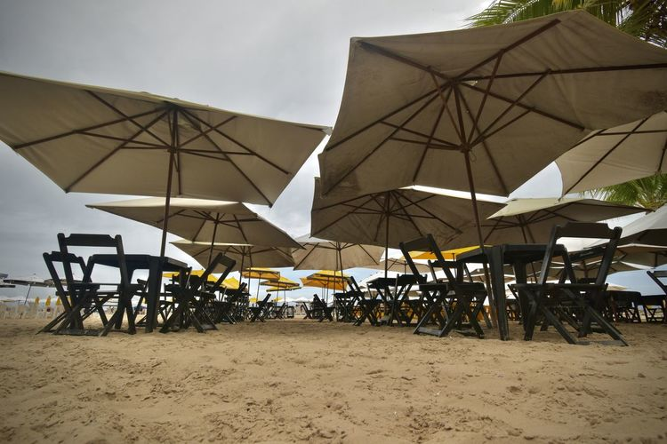 Chairs and tables on beach against sky