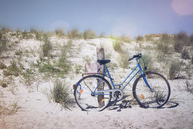 Bicycle Parked On Sand Against Sky