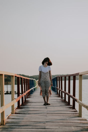 Rear view of woman on pier against sky