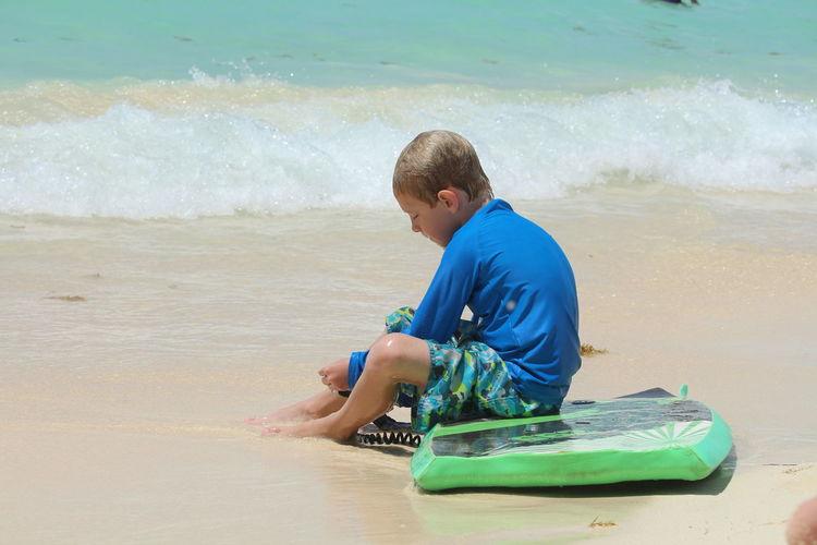 Boy with surfboard sitting on beach