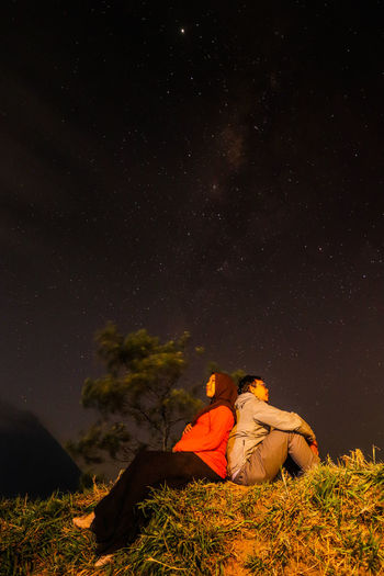 Rear view of couple sitting on field against sky at night