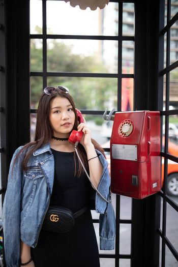 Portrait of woman making calling in telephone booth