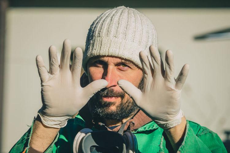Portrait of man wearing gloves gesturing outdoors