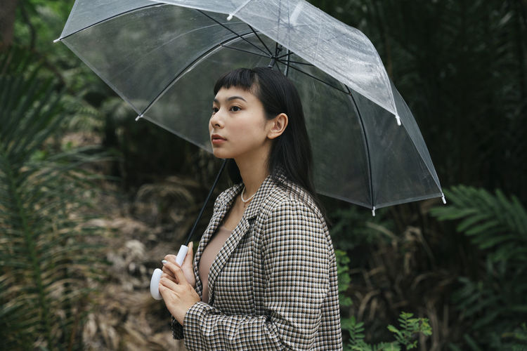 Young woman looking away while standing on rainy day