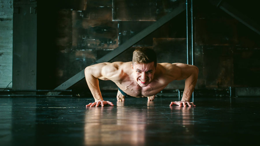 Portrait of shirtless muscular man doing push-ups at home