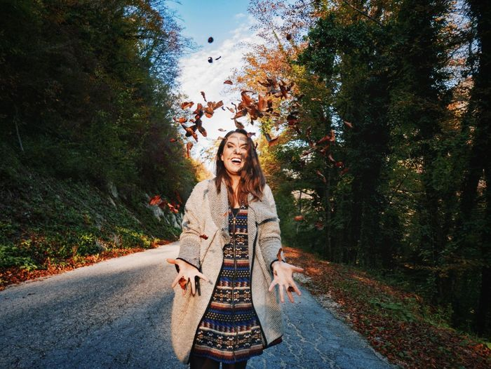 Portrait of smiling young woman by road against trees