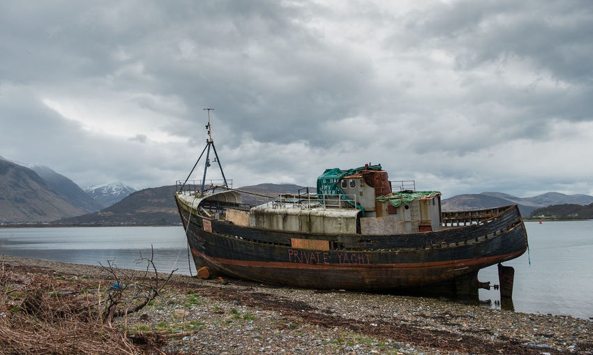 Abandoned Shipwreck On Lakeshore Against Cloudy Sky
