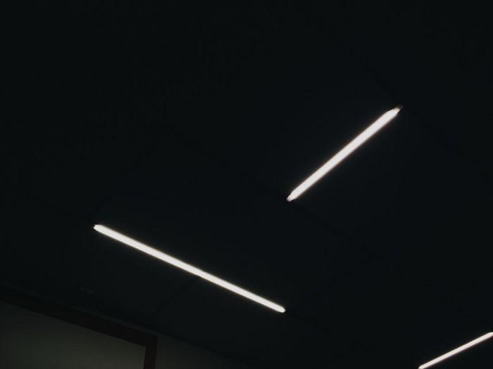 Low angle view of illuminated lamp at night