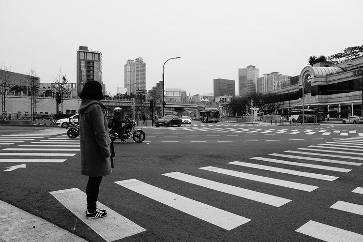 Man crossing road against city street