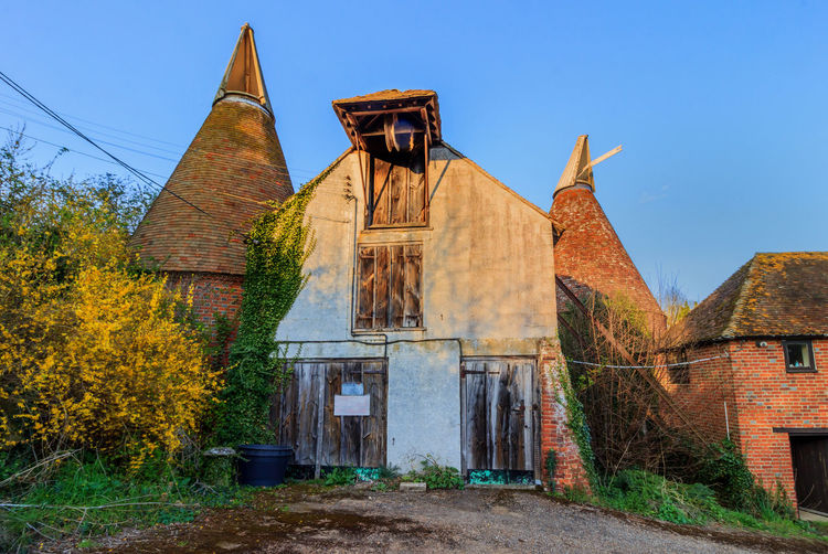 Elbridge Oast House, Kent, England. Oast House Garden Of England Travel Destinations Tourism Farm Hops Farm Yard Beer Brewing History Drying Kilm Barn Hop Pocket Celler Countryside Rural Scene Getty Images EyeEm Gallery Architecture Abondoned Built Structure Building Exterior Sky Building Plant Belief Religion Nature Place Of Worship Spirituality Day Old No People The Past Clear Sky Blue Tree Outdoors