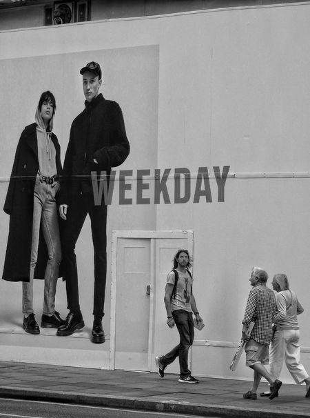 Full Length Text Communication Togetherness People Men Adult Outdoors Adults Only Day Standing Walking Weekday Hoarding Monochrome Black And White Poster Stepping Out Doorway Advertising Words Daytime Cool Comparison The Street Photographer - 2017 EyeEm Awards