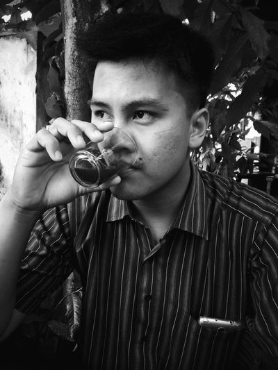 Young man drinking juice in glass against trees