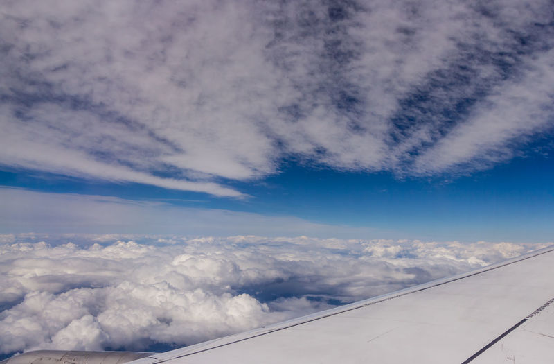 Aerial view of cloudscape over airplane wing