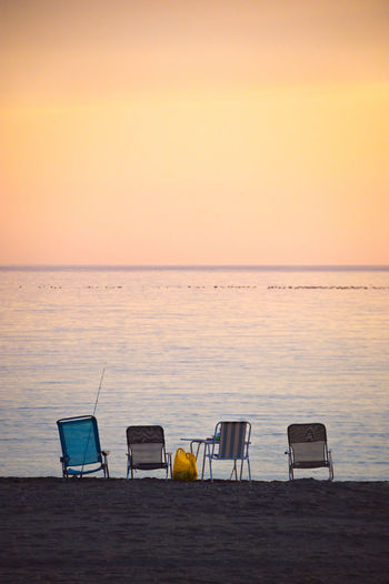 Chairs on beach against sky during sunset