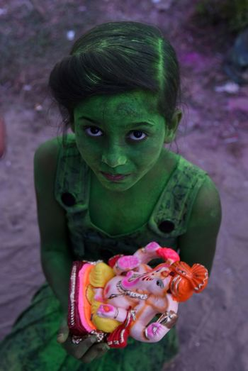 Allahabad: A devotee react to camera as she hold Elephant headed Hindu God Ganesha's before immersing idol in a pond on the ocassion of Anant Chaturdasi festival celebration in Allahabad. Celebration Childhood Close-up Day Elementary Age Face Paint Front View Green Color High Angle View Holi Lifestyles Looking At Camera One Person Outdoors People Portrait Real People Traditional Festival Young Adult Young Women