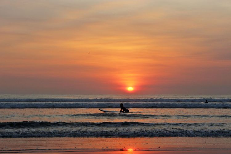 Person surfing in sea against cloudy sky during sunset at kuta