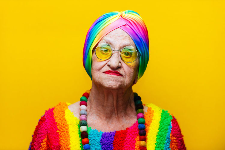 Portrait of woman wearing colorful clothing against yellow background