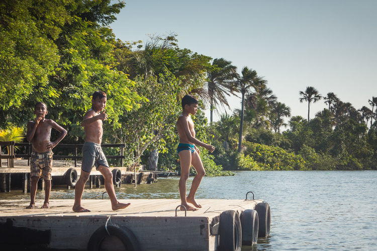These boys had a really good time when we were passing by, by boat. Boys Clear Sky Day Friendship Growth Jungle Lake Leisure Activity Nature Outdoors People Pier Real People Shirtless Sky Standing Streetphotography Togetherness Travel Travel Photography Traveling Tree Walking Water Young Adult The Street Photographer - 2017 EyeEm Awards The Photojournalist - 2017 EyeEm Awards The Portraitist - 2017 EyeEm Awards EyeEmNewHere This Is Masculinity This Is Latin America
