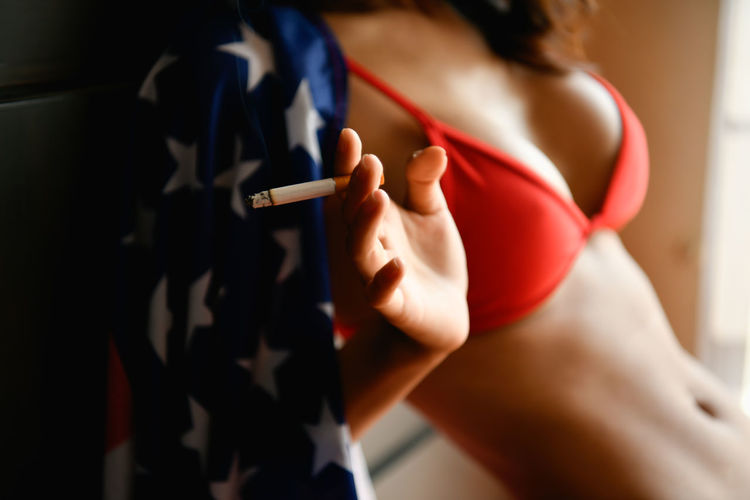 Midsection of sensuous woman holding cigarette