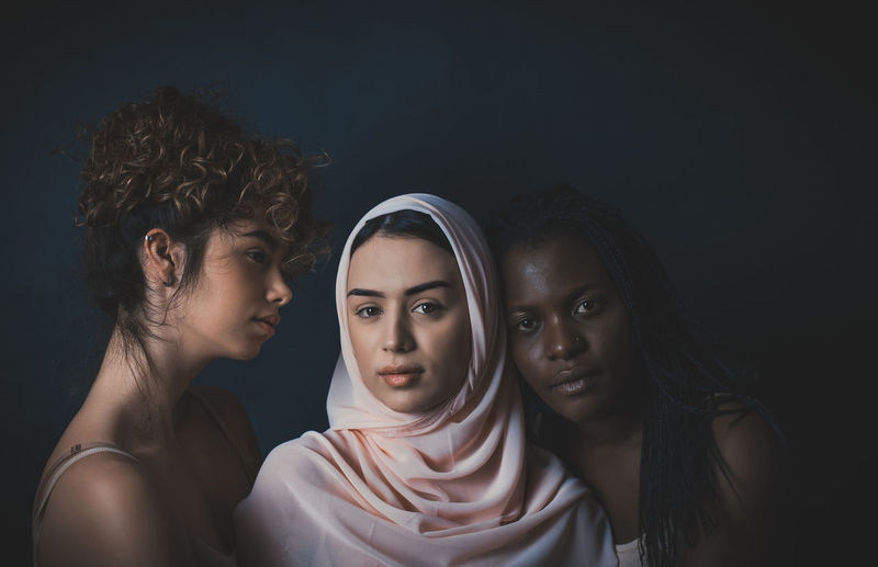 Portrait of young couple against black background
