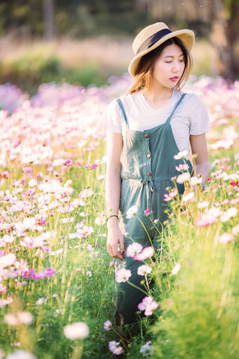 Young woman standing amidst flowering plants on field