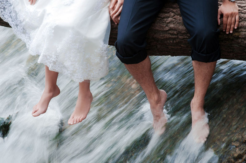 Low section of man and woman in water
