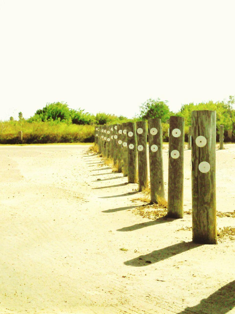Wooden Post On Beach Against Clear Sky