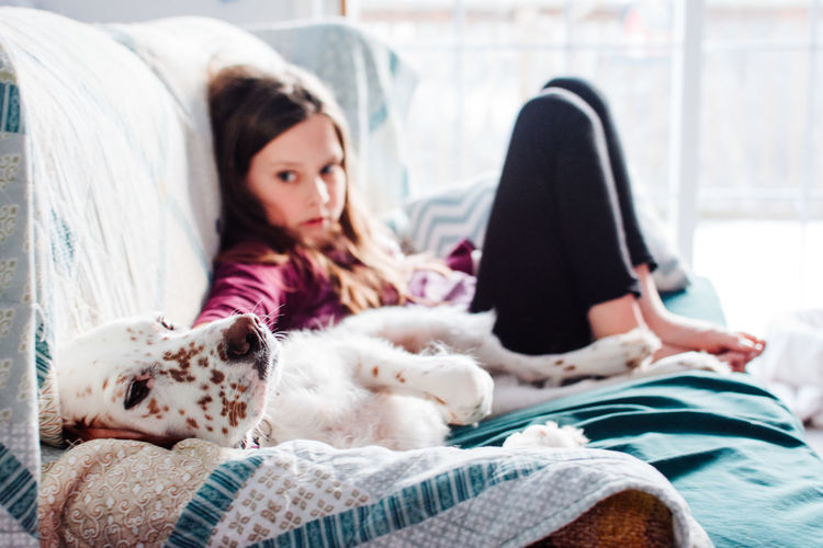 Animal Themes Bed Bedroom Casual Clothing Close-up Day Dog Domestic Animals Home Interior Indoors  Looking At Camera Lying Down Mammal One Animal One Person One Young Woman Only People Pets Pillow Portrait Real People Relaxation Sitting Young Adult Young Women